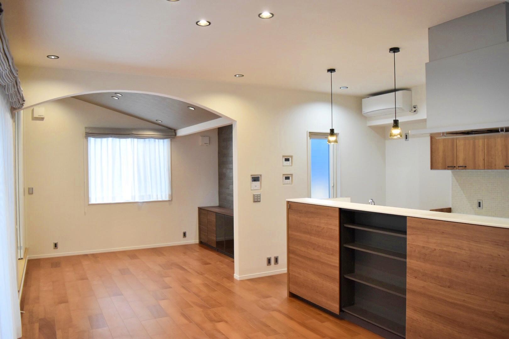 玄関ホールから扉を開けるとLDKへ。 Rの下り壁と勾配天井のある開放的で華やかな空間。